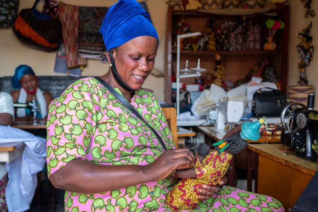A member of the Rwandan Art cooperative is sewing a doll. Thanks to the gained income she can strenghten her self-reliance.